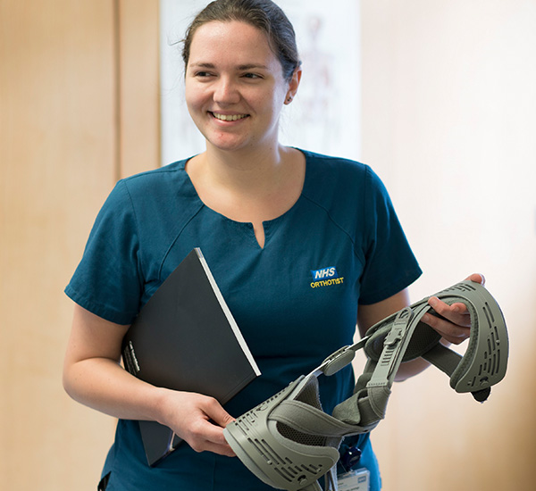 Female orthotist holding equipment