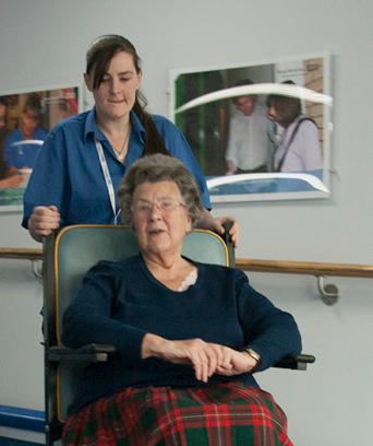 Female in uniform transporting an elderly female in wheelchair
