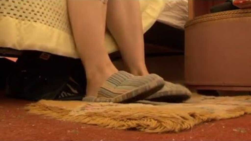 Close-up of person's legs in slippers