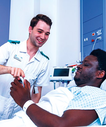 Male adult nurse tending to patient in bed