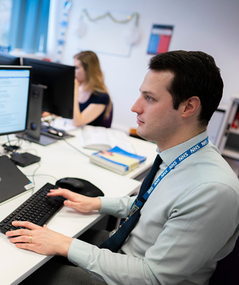 Male sitting at desk looking at computer