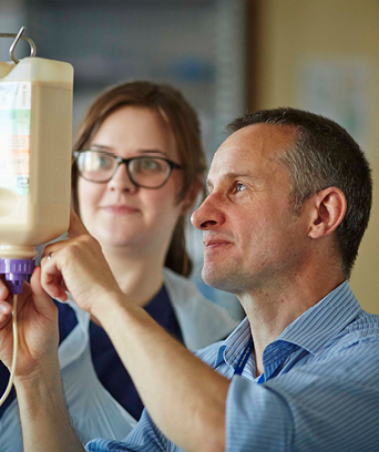 Two NHS staff members looking at hospital drip pouch