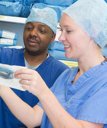 Two NHS staff members in scrubs looking at equipment