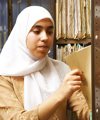 Female in headscarf putting document on shelf