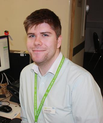 Male sitting at desk smiling at camera