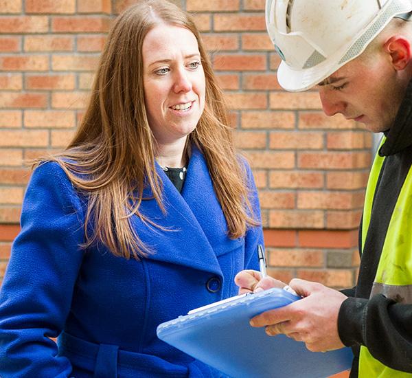 Female manager talking to man in high vis vest