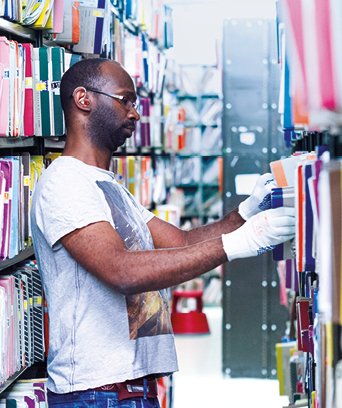 Male in gloves tidying documents on library shelves