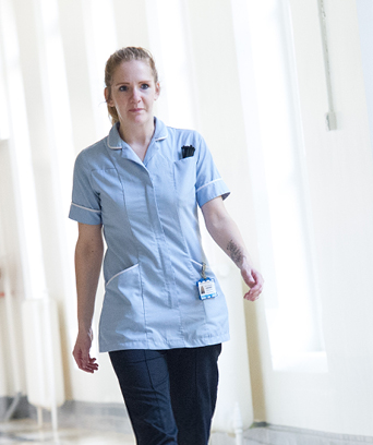 Female in uniform walking down hospital corridor