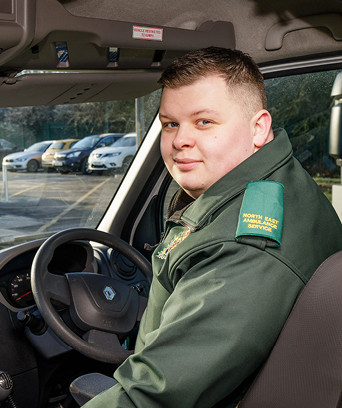Male paramedic sitting in driver's seat of ambulance