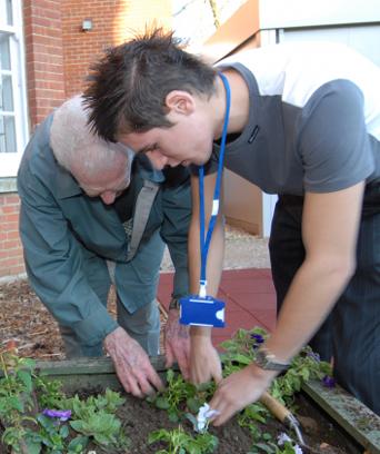 Male NHS staff member tending garden with elderly man