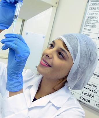 Female in lab coat looking at sample
