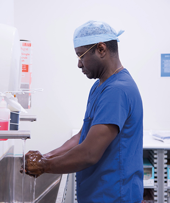 Male surgeon in scrubs washing hands