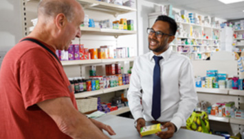 Male pharmacist talking to customer over counter