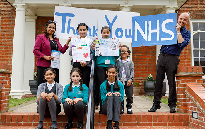 Primary school pupils holding 'Thank you NHS' sign